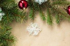Festlig jul gränsar med röda bollar på granfilialer och snöflingor på lantlig beige bakgrund Arkivbilder