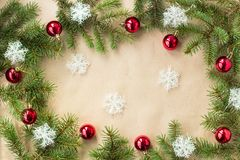 Festlig jul gränsar med röda bollar på granfilialer och snöflingor på lantlig beige bakgrund Royaltyfri Bild