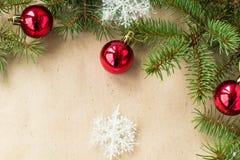 Festlig jul gränsar med röda bollar på granfilialer och snöflingor på lantlig beige bakgrund Royaltyfri Foto