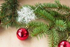 Festlig jul gränsar med röda bollar på granfilialer och snöflingor på lantlig beige bakgrund Arkivfoton