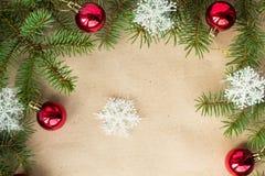 Festlig jul gränsar med röda bollar på granfilialer och snöflingor på lantlig beige bakgrund Arkivfoto