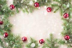 Festlig jul gränsar med röda bollar på granfilialer och snöflingor med snö på lantlig beige bakgrund Royaltyfri Foto