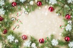 Festlig jul gränsar med röda bollar på granfilialer och snöflingor med snö på lantlig beige bakgrund Royaltyfria Bilder