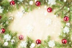 Festlig jul gränsar med röda bollar på granfilialer och snöflingor med snö på lantlig beige bakgrund Royaltyfria Foton