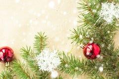 Festlig jul gränsar med röda bollar på granfilialer och snöflingor med snö på lantlig beige bakgrund Arkivbild