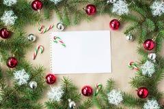Festlig jul gränsar med röda och silverbollar på granfilialer och snöflingor på lantlig beige bakgrund Fotografering för Bildbyråer