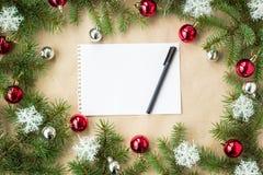 Festlig jul gränsar med röda och silverbollar på granfilialer och snöflingor på lantlig beige bakgrund Royaltyfri Fotografi