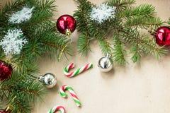 Festlig jul gränsar med röda och silverbollar på granfilialer och snöflingor på lantlig beige bakgrund Arkivbild