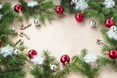 Festlig jul gränsar med röda och silverbollar på granfilialer och snöflingor på lantlig beige bakgrund Royaltyfri Bild