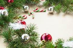 Festlig jul gränsar med röda och silverbollar på granfilialer och snöflingor på lantlig beige bakgrund Arkivfoton
