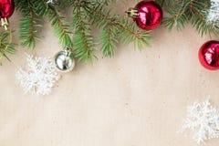 Festlig jul gränsar med röda och silverbollar på granfilialer och snöflingor på lantlig beige bakgrund Royaltyfri Foto