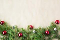 Festlig jul gränsar med röda och silverbollar på granfilialer och snöflingor på lantlig beige bakgrund Arkivfoto
