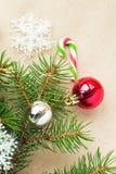 Festlig jul gränsar med röda och silverbollar på granfilialer och snöflingor på lantlig beige bakgrund Arkivbilder