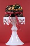 Festlig jul mat, fruktkaka med glace körsbär och muttrar på den vita kakan mot en röd bakgrund Royaltyfria Bilder