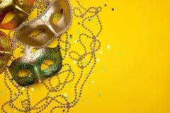Festlig karnevalgräsplan och guldmaskeringar och pärlor på en guling tillbaka royaltyfri bild