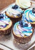 Festlig muffin på en träbakgrund med det ljusa kräm och blåbäret med en lantlig stil för stearinljus Royaltyfria Foton