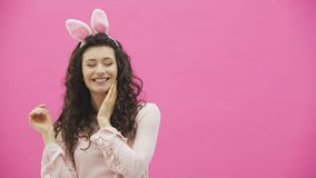 Festlig påsksemesterperiod Le den unga kvinnan i öron för påskkanin på rosa bakgrund som hoppar och ser kopian