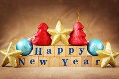 Festlig sammansättning för lyckligt nytt år med en text som ordnas av träkuber och färgrika garneringar arkivbild