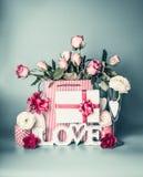 Festlig sammansättning med ordet FÖRÄLSKELSE som hälsar asken med det röda bandet, shoppingpåse med rosor, blommar, emballagegarn arkivfoton