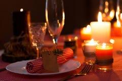 Festlig sammansättning med stearinljus och plattor tabell för garneringservettplatta En härlig tabellinställning, röd tabelltorkd Fotografering för Bildbyråer