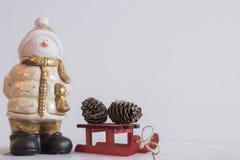 Festlig snögubbeleksak på en ljus bakgrund med röda slädar och kottar Beröm av jul och det nya året placera text tomt fotografering för bildbyråer