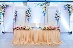 Festlig tabell för bruden och brudgummen som dekoreras med torkduken och blommor royaltyfria foton