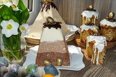 Festlig tabell f?r p?sk Mycket p?skkakor fr?n ostmassadeg som dekoreras med choklad- och chokladvaktel?gg, royaltyfri fotografi
