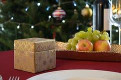 Festlig tabell med en gåvaask och en dekorerad julgran i bakgrund arkivbild