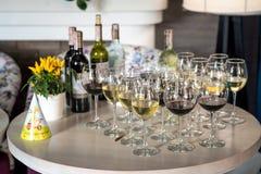 Festlig tabell med exponeringsglas av vin, kylde flaskor av vin arkivbilder