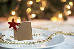 Festlig tabell som dekoreras med det julbollar och kortet för wina Arkivfoton