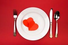 Festlig tabellinställning för valentin dag med gaffeln, kniv, hjärtor på en röd bakgrund Top beskådar - Bild royaltyfria foton