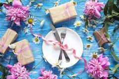 Festlig tabellinställning med bestick, pioner och gåvaaskar på bl Royaltyfri Foto