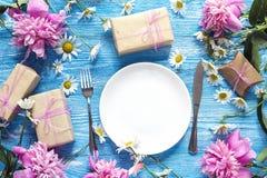 Festlig tabellinställning med bestick, pioner och gåvaaskar på bl Fotografering för Bildbyråer
