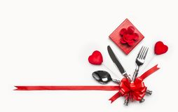 Festlig tabellställeinställning med bestick och röd pilbåge och band, gåvaask och hjärtor på vit bakgrund, baner Orientering för  arkivbild