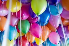 festliga färgrika ballonger med heliumtillbehöret till de vita banden Royaltyfri Foto