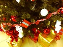 Festliga färgrika härliga skinande gåvaaskar, garneringar under det gröna trädet för jul med visare och filialer, leksaker royaltyfri foto