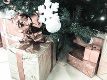 Festliga färgrika härliga skinande gåvaaskar, garneringar under det gröna trädet för jul med visare och filialer, leksaker arkivfoto