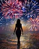 Festliga fyrverkerier över havs- och silhouettekvinna royaltyfri foto