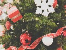 Festliga mångfärgade härliga skinande utsmyckade bollar, leksaker, gåvaaskar, garneringar på det gröna trädet för jul med visare royaltyfria foton