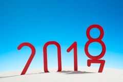 Festliga nya år solig tropisk strand för begrepp med det ändrande datumet 2017 - 2018 i röd och kopieringsutrymme på en blå himme Arkivbild