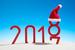 Festliga nya år solig tropisk strand för begrepp med det ändrande datumet 2017 - 2018 i röd och kopieringsutrymme på en blå himme Royaltyfri Bild