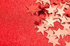 Festliga stjärnor på rött Arkivfoto