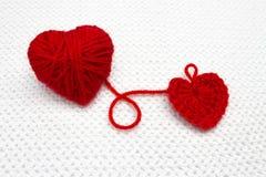 Festligt foto som sticker med förälskelse Handgjord virkninghjärta och röd garnboll som en hjärta på den vita virkningbakgrunden  Royaltyfria Foton