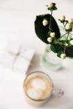 Festligt morgonkaffe och en gåva för en kvinna med en blomma Royaltyfri Bild