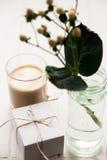 Festligt morgonkaffe och en gåva för en kvinna med en blomma Arkivfoto