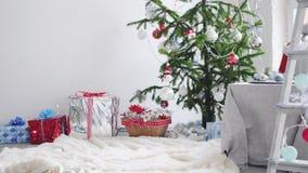 Festligt sparkly confetty falla för jul ner på bakgrunden av julgranen och gåvaaskarna långsam rörelse stock video
