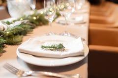 Festmåltid A för julmatställen dekorerade att äta middag tabellen med champagneexponeringsglas- och julträdet i bakgrund royaltyfria bilder