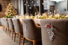 Festmåltid A för julmatställen dekorerade att äta middag tabellen med champagneexponeringsglas- och julträdet i bakgrund fotografering för bildbyråer