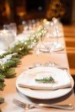 Festmåltid A för julmatställen dekorerade att äta middag tabellen med champagneexponeringsglas- och julträdet i bakgrund royaltyfri bild