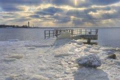 Festmachen im Eis gegen einen Leuchtturm im Winter lizenzfreies stockbild